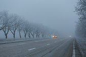 Cars with turned on headlights at road on foggy morning