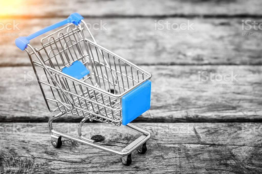 Cart from the grocery store on the old wooden background stock photo