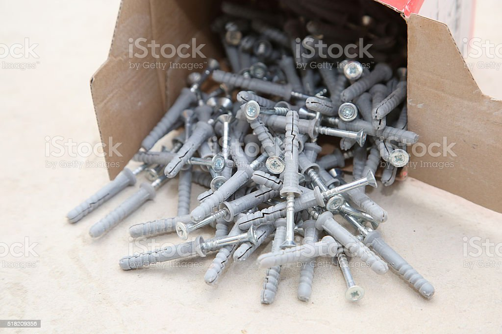 carton box ful of screws with wall plugs stock photo