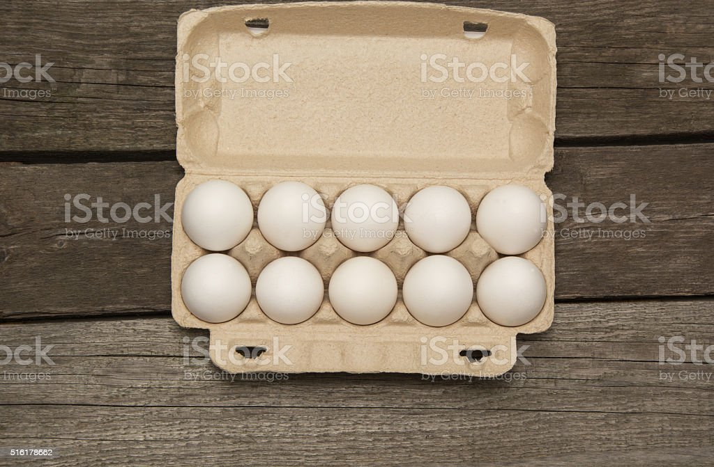 Carton of eggs on wooden background. Top view. stock photo
