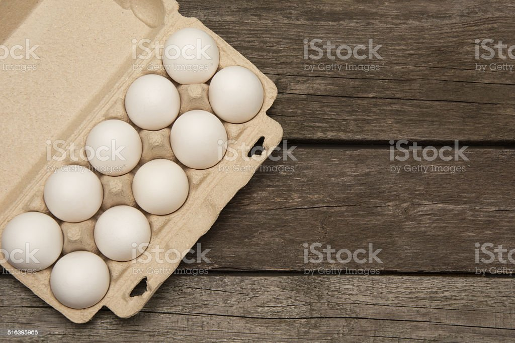Carton of organic eggs on wooden background. Top view. stock photo