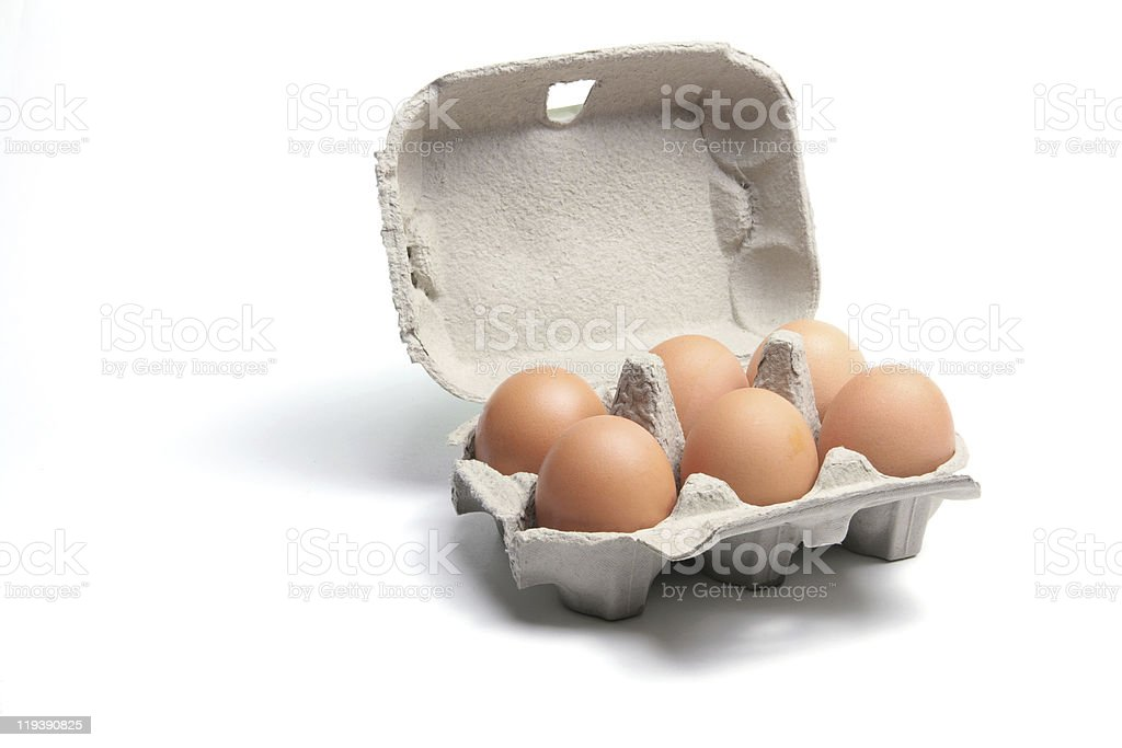 Carton of six brown eggs on white background stock photo