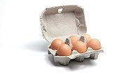 Carton of six brown eggs on white background