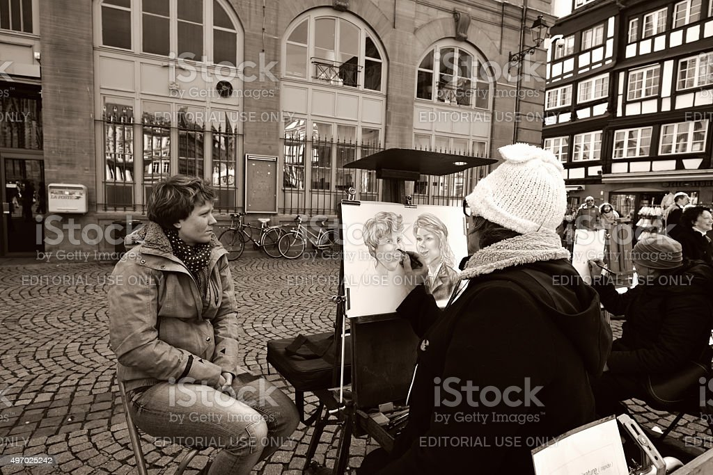 Cartoonist at work on street stock photo