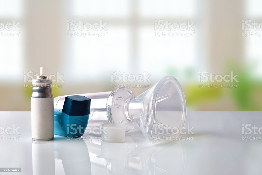 Cartridge inhaler and chamber and mask in room front view stock photo