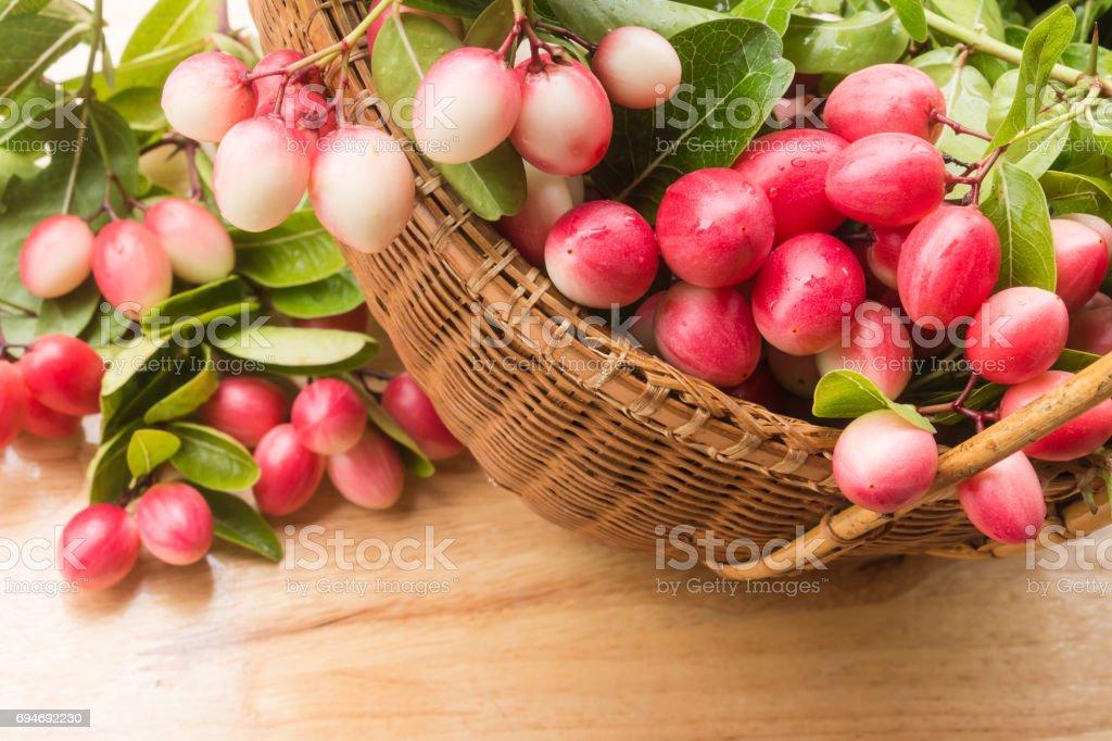 Carunda or Karonda fruits in the basket on wood background stock photo