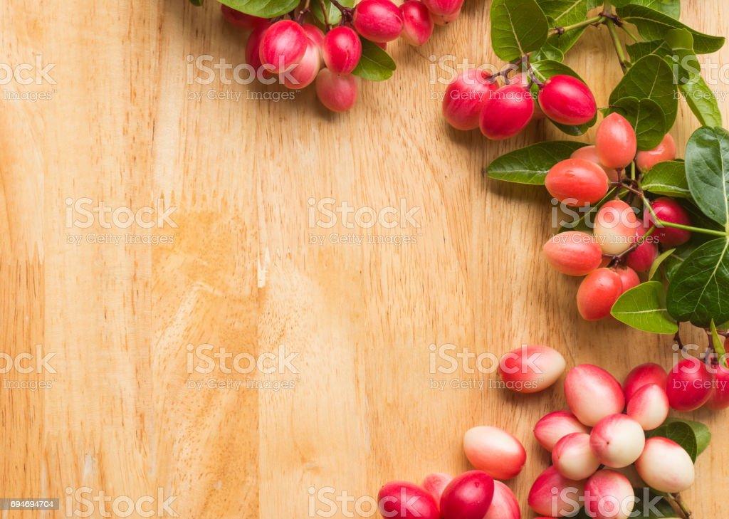 Carunda or Karonda fruits on wood background stock photo