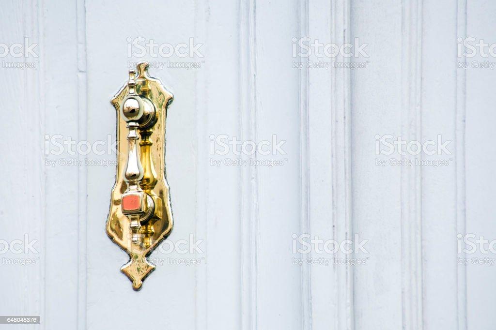 Carved ancient door knocker on white door. stock photo