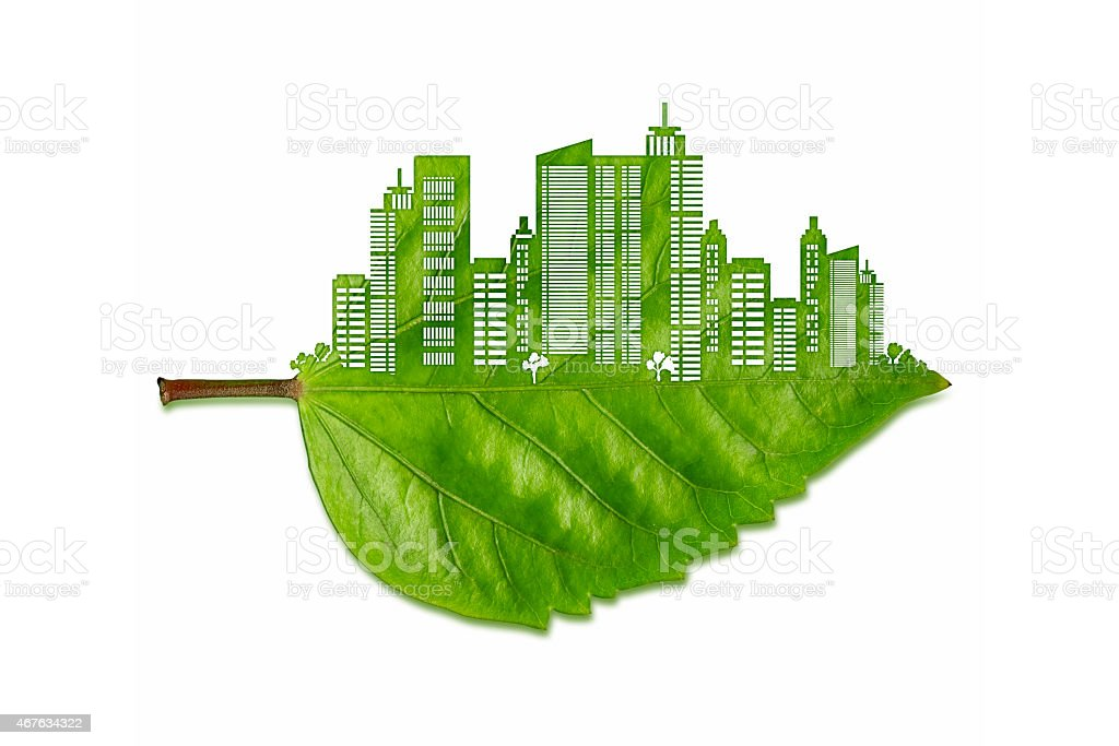 Carved green leaf with a big city silhouette. stock photo