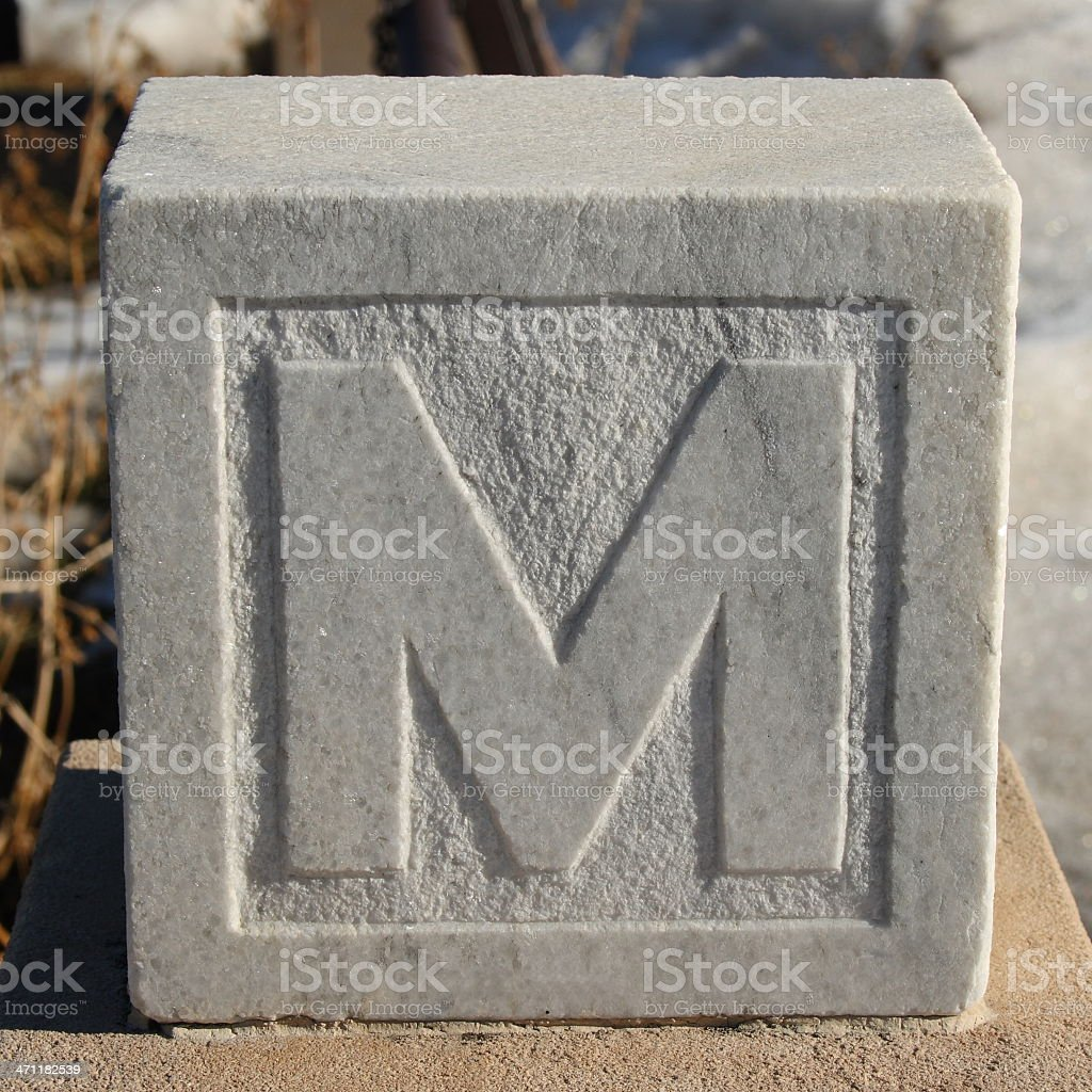 'M' carved into a marble square cemetary marker royalty-free stock photo