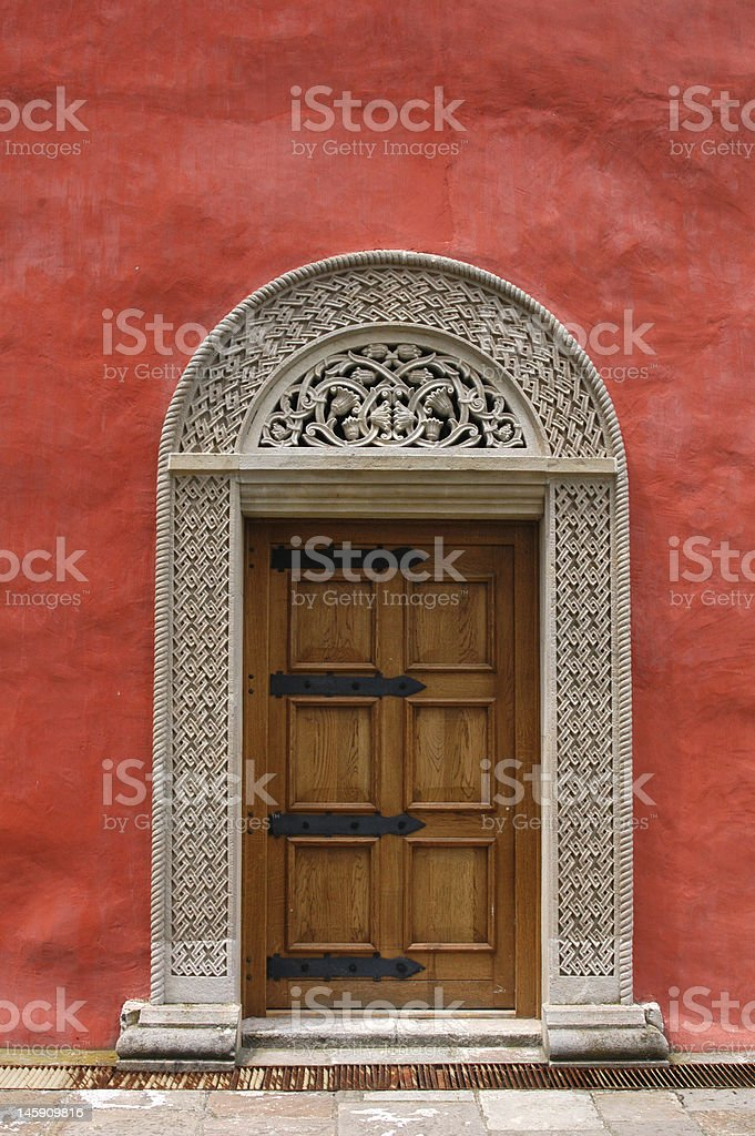 Carved Medieval Door in the Red Stucco Wall royalty-free stock photo
