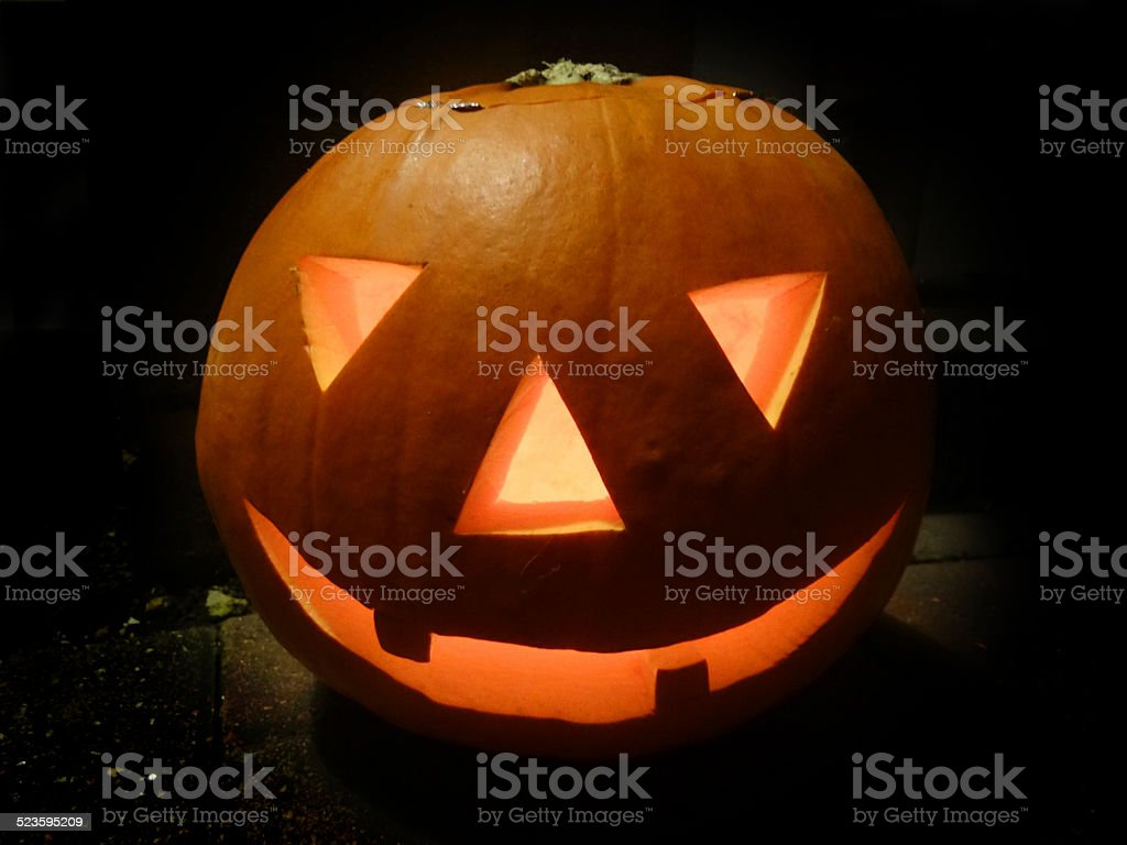 Carved pumpkin head image, scary Halloween face, candle, illuminated glowing-orange stock photo