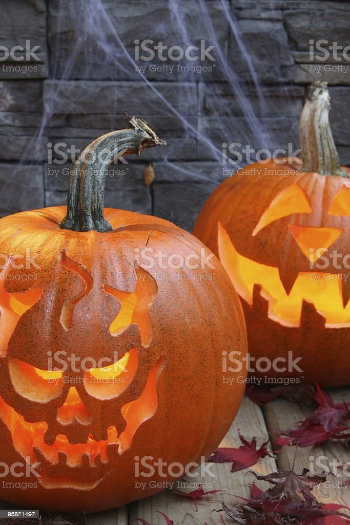 Carved pumpkins, 2 lit Halloween theme royalty-free stock photo