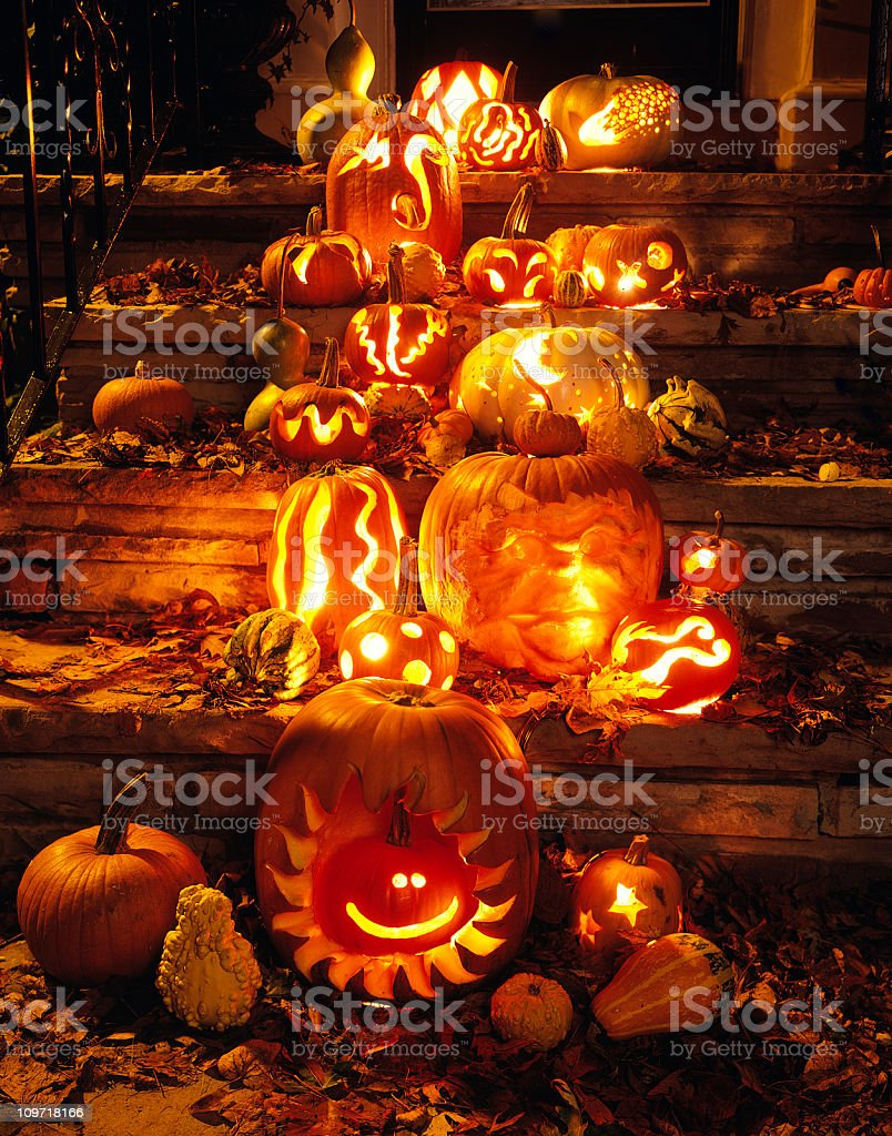 Carved Pumpkins and Autumn Leaves on Steps to House stock photo