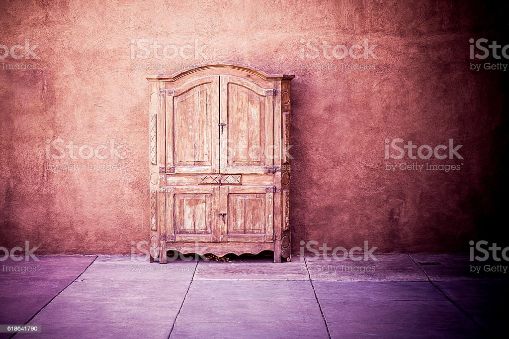 Carved rustic wardrobe against plastered wall in empty room stock photo