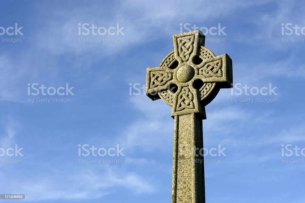 Carved stone celtic cross against a blue sky with cloud. royalty-free stock photo