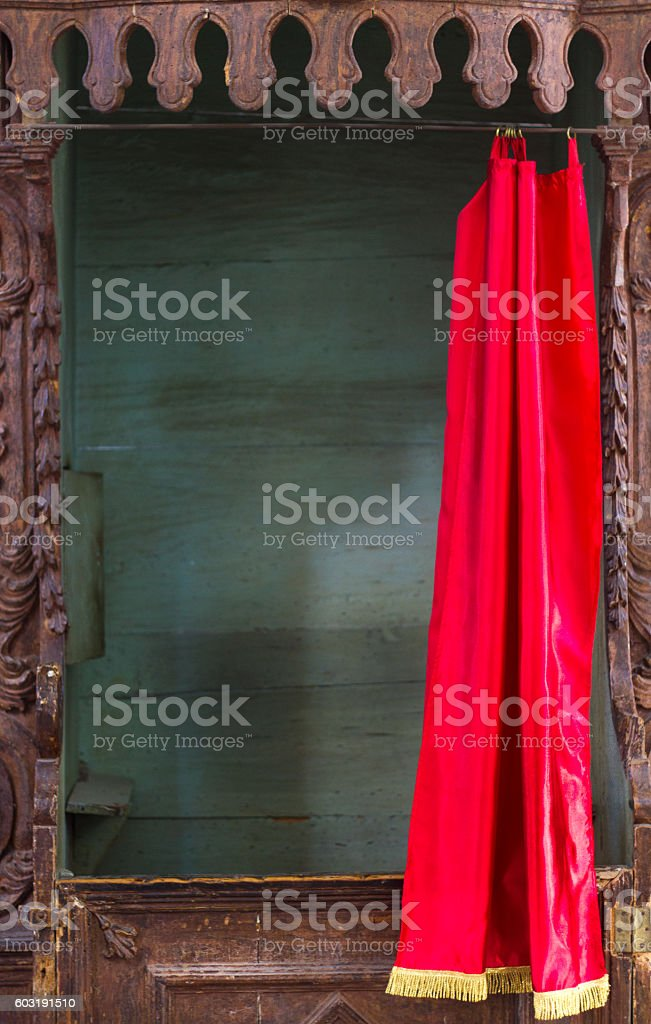 Carved Vintage Wooden Confession Booth with Bright Red Curtain stock photo