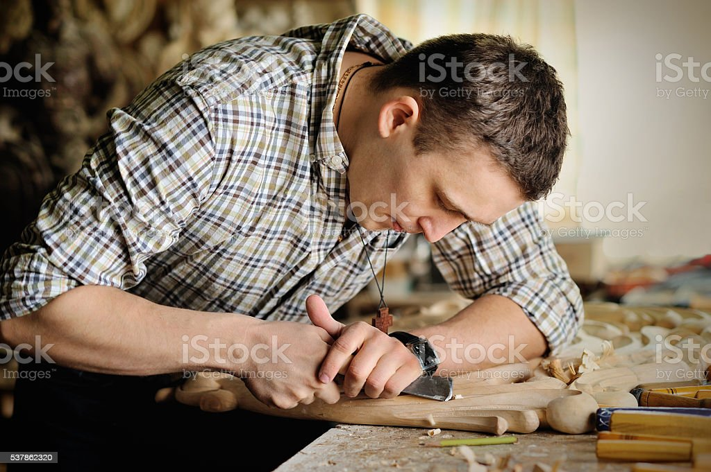 Carver in workshop of wood carving stock photo