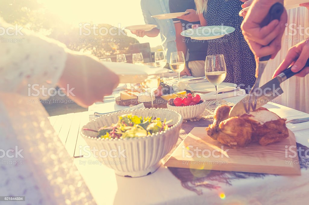 Carving a chicken with friends and family. stock photo