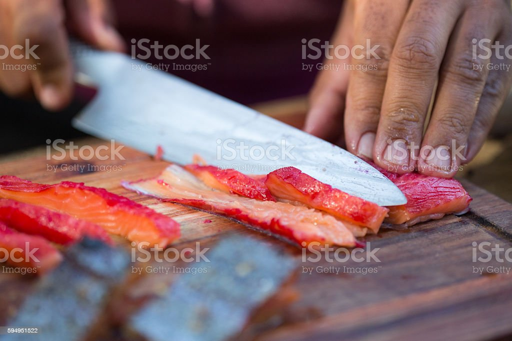 Carving Beetroot Cured Trout stock photo
