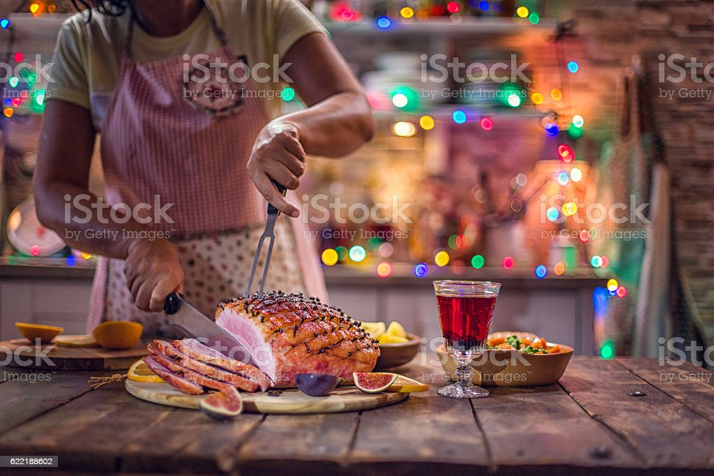 Carving Glazed Holiday Ham with Cloves stock photo