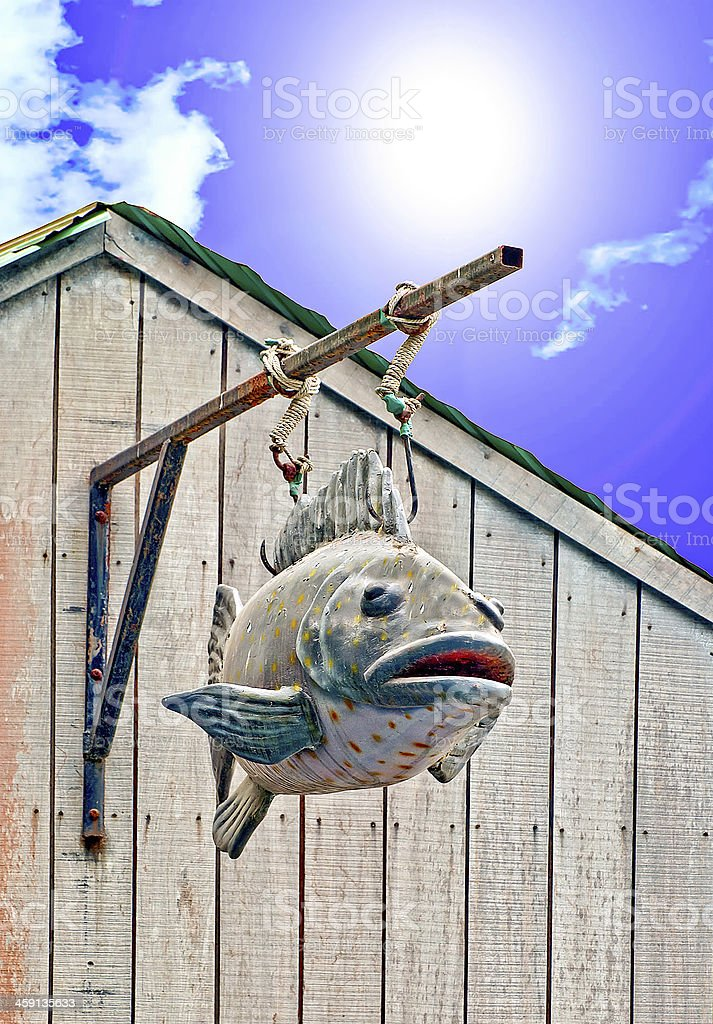 Carving of  fish with hook on blue sky background royalty-free stock photo