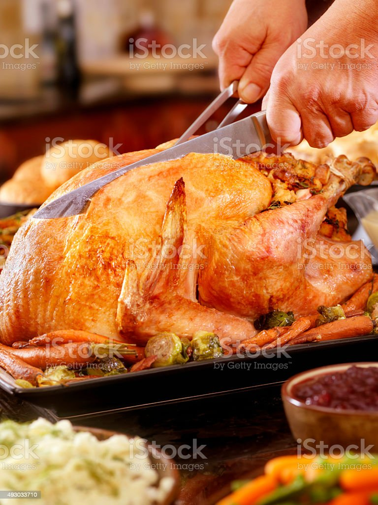 Carving Turkey Dinner with Stuffing and All the Fixings stock photo