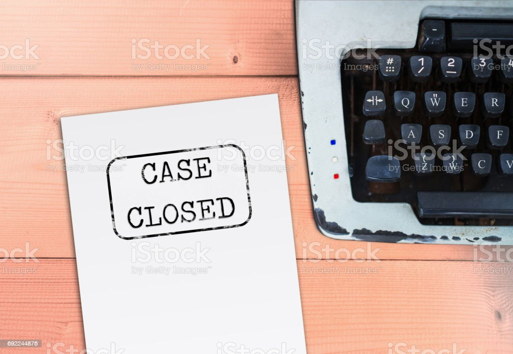 Case closed on paper with typewriter on wooden table stock photo