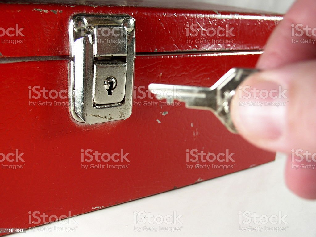 Cash box, locked, with person holding key to unlock stock photo