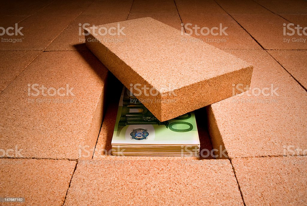 Cash hiding under a brick in the floor stock photo