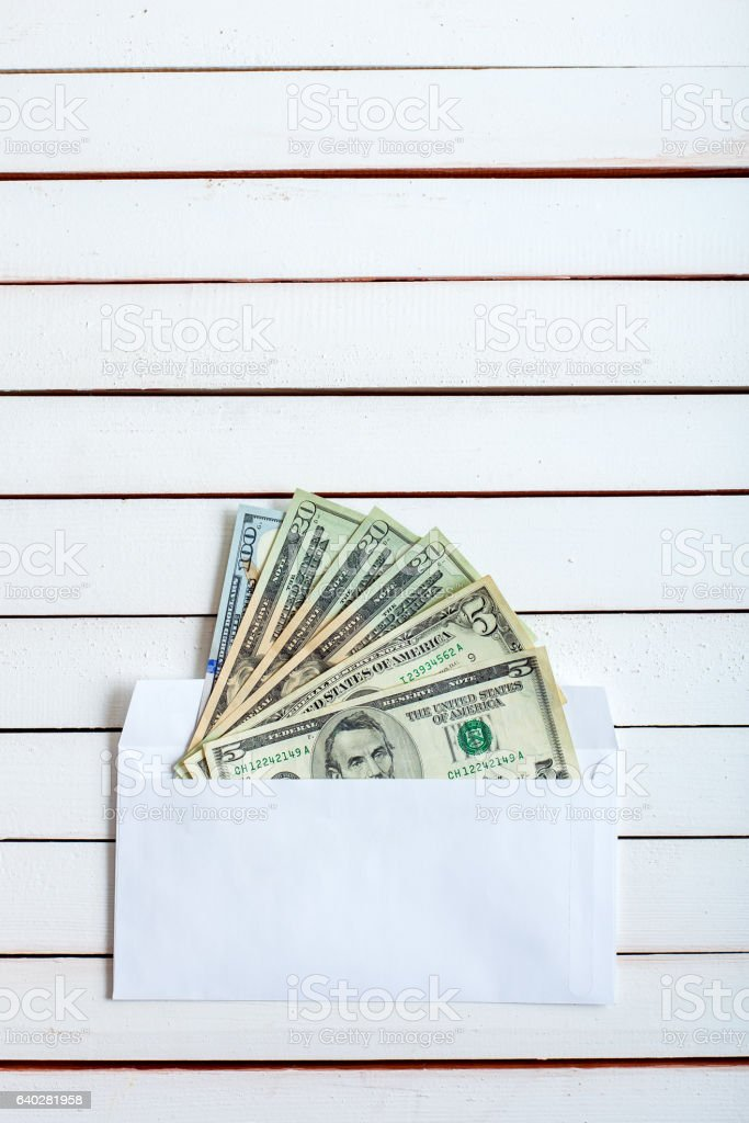 Cash in an envelope on white wooden table. stock photo