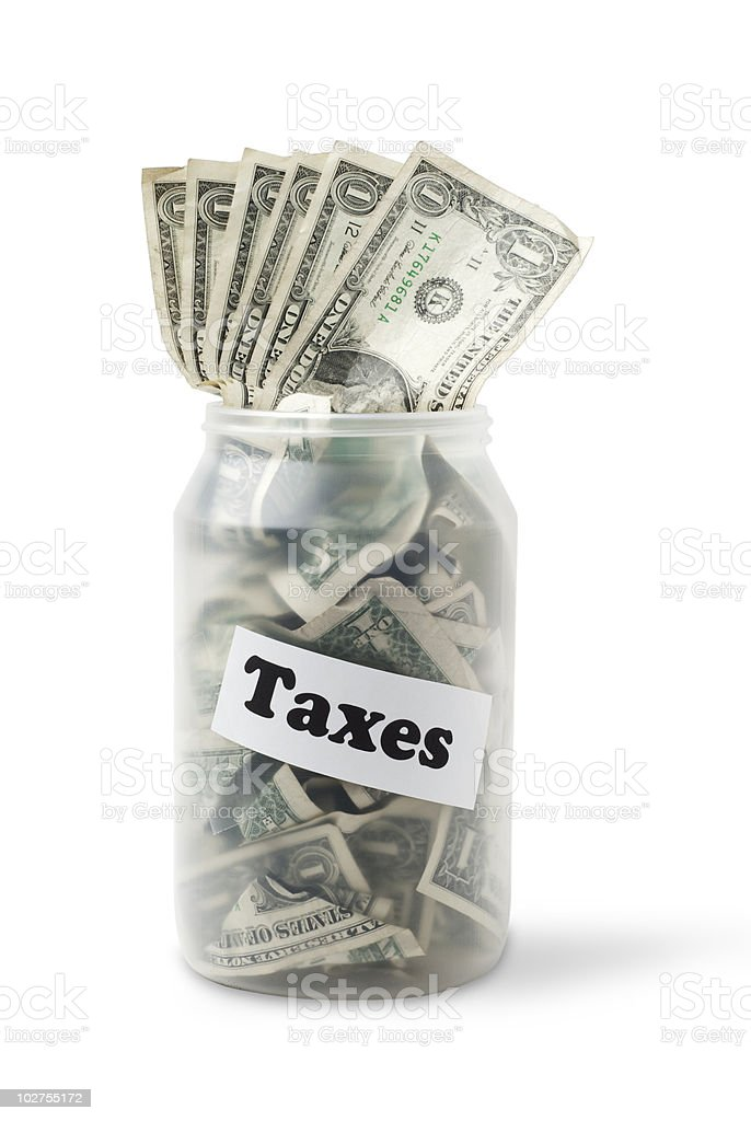 """Cash jar with US Dollar Bills and a sign """"Taxes"""" royalty-free stock photo"""