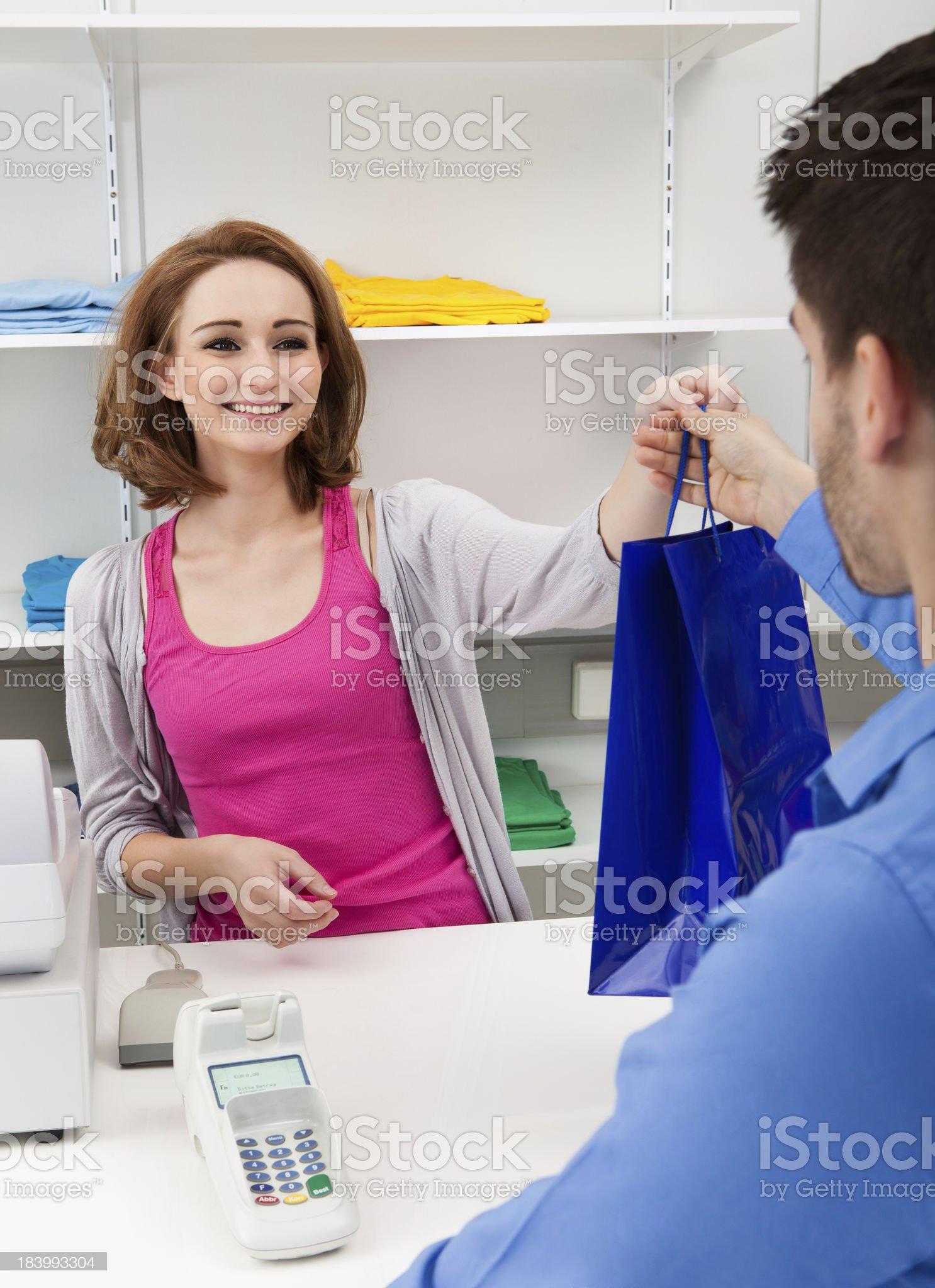 Cashier Handing Over Shopping Bag To Customer royalty-free stock photo