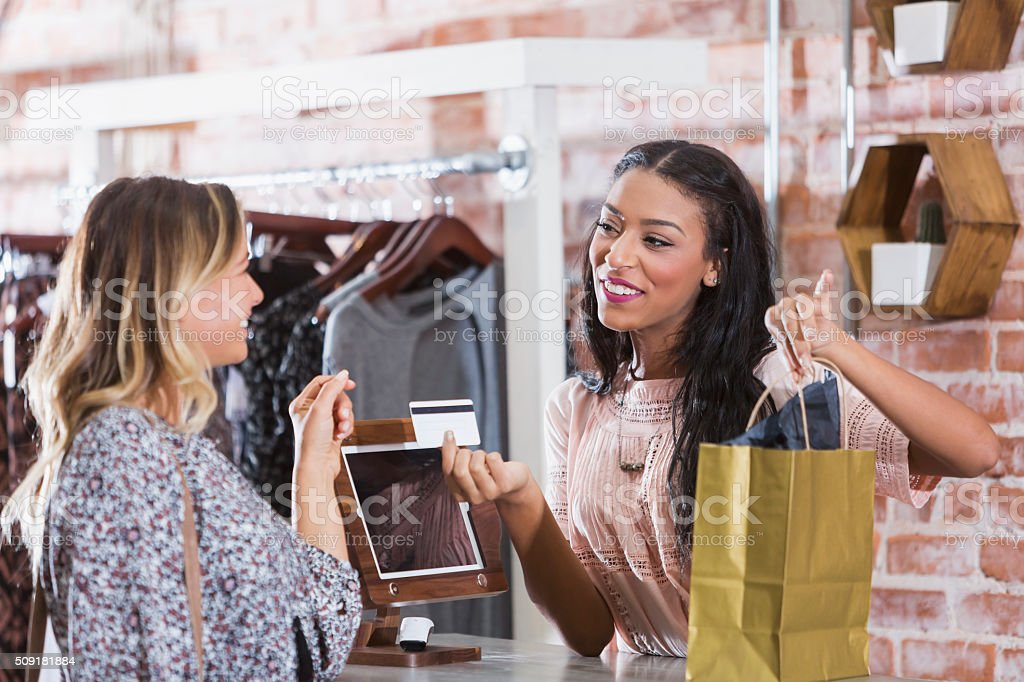 Cashier helping customer at checkout counter of store stock photo