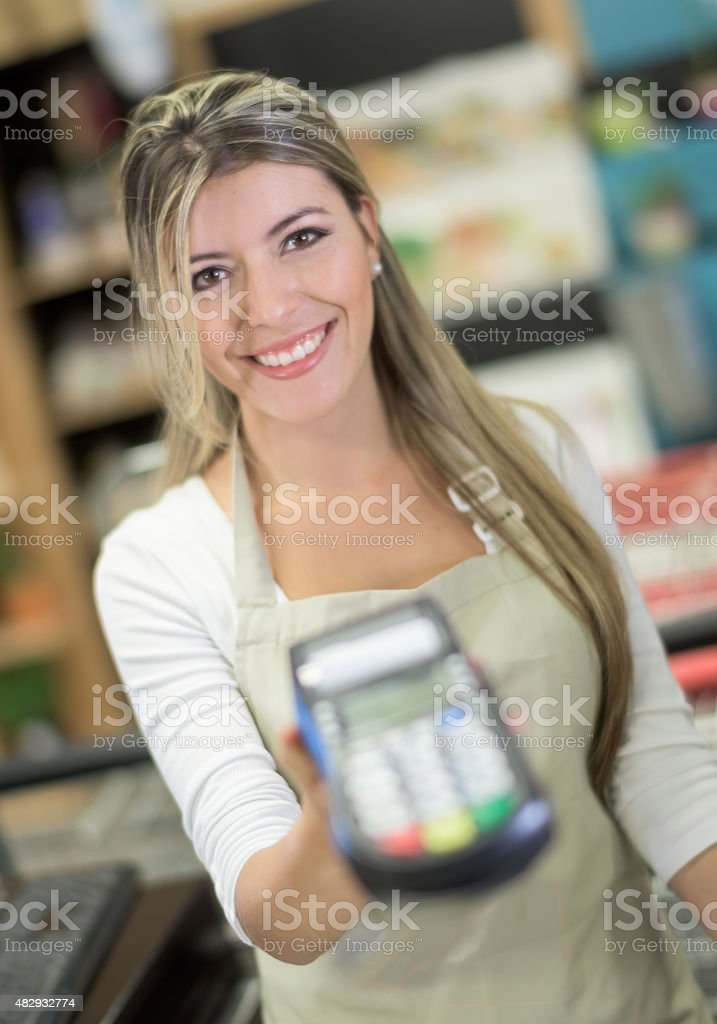 Cashier holding a credit card reader machine stock photo