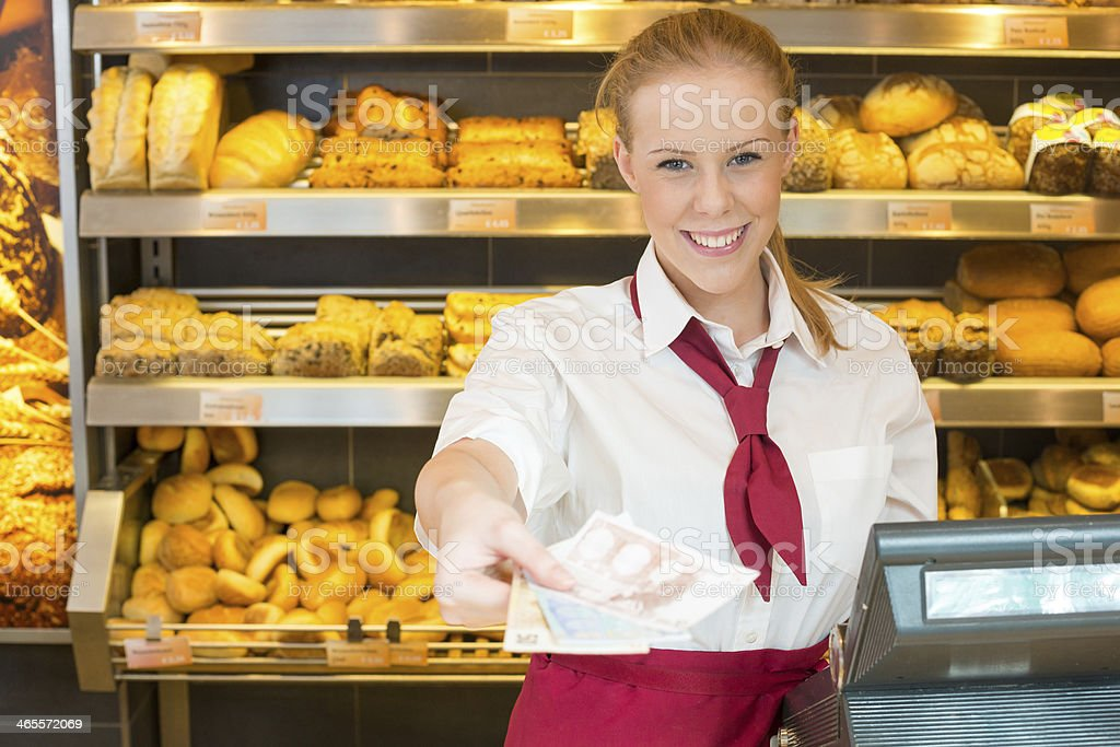 Cashier in bakery giving money to customer royalty-free stock photo