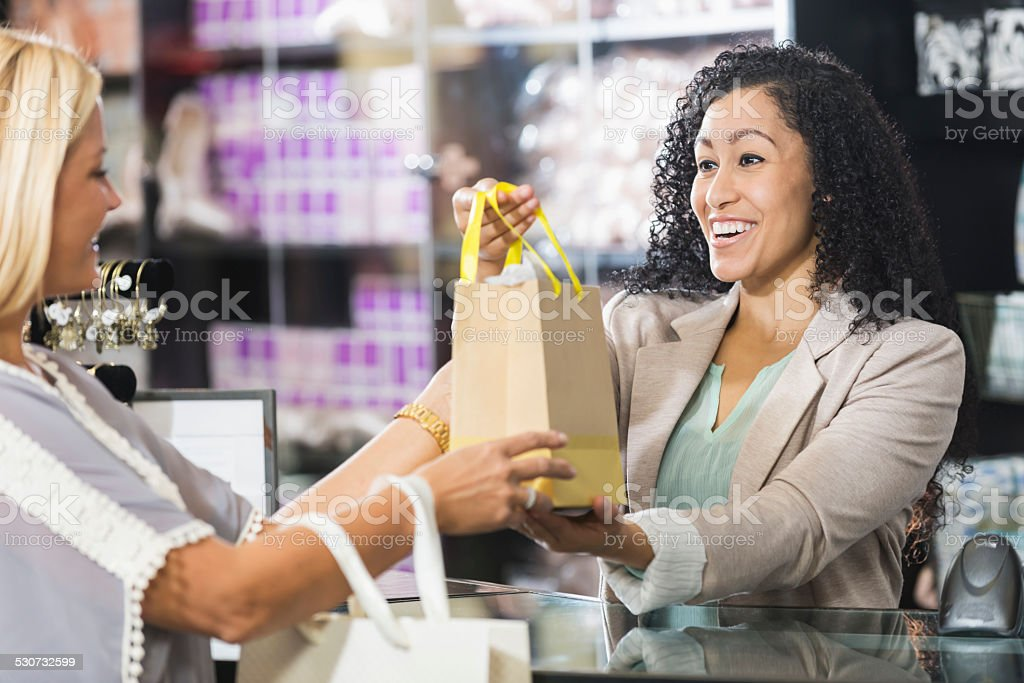 Cashier In Retail Store Handing Customer Shopping Bag stock photo ...