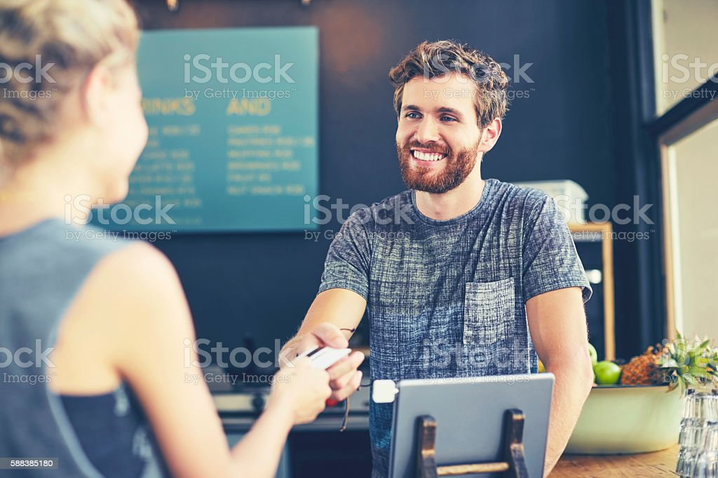 Cashier looking at customer while receiving card stock photo