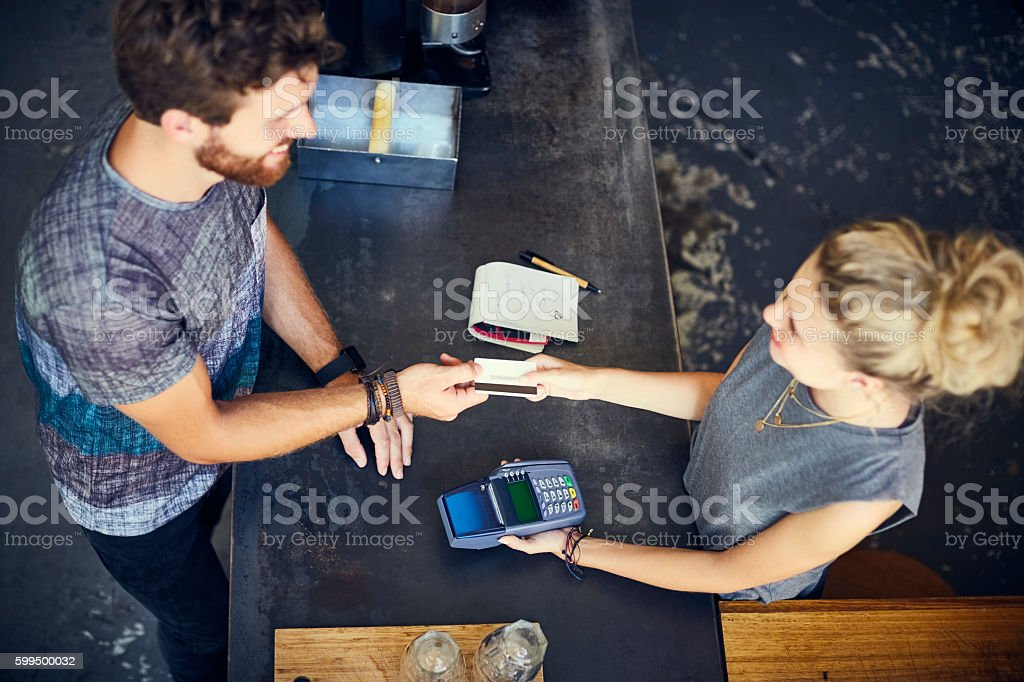 Cashier receiving credit card from man in cafe stock photo