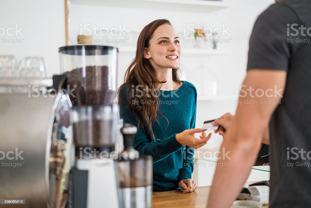 Cashier receiving payment from customer in cafe stock photo