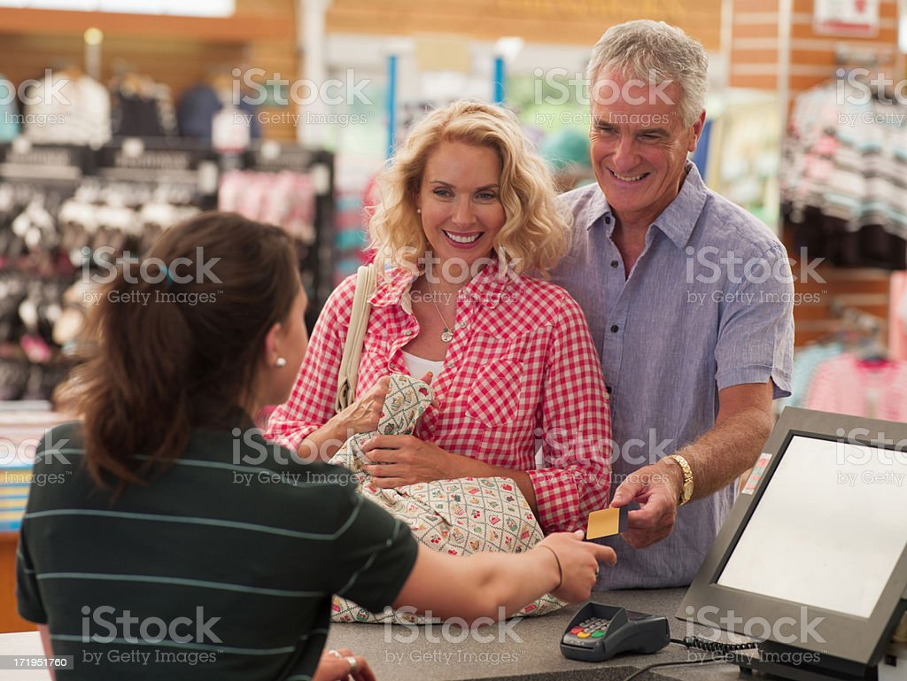 Cashier scanning couple's purchases in store royalty-free stock photo