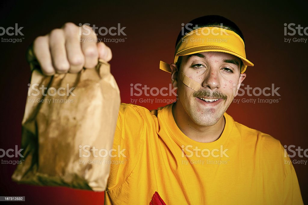 Cashier serving a greasy paper bad of junk food stock photo