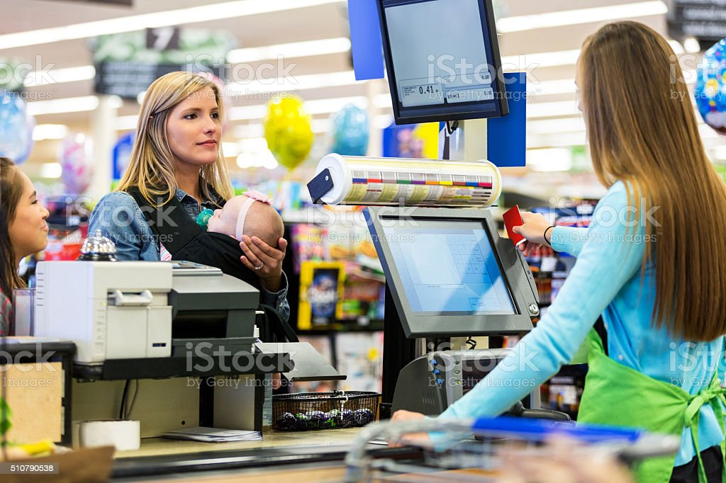 Cashier swiping loyalty card for mother in grocery store stock photo