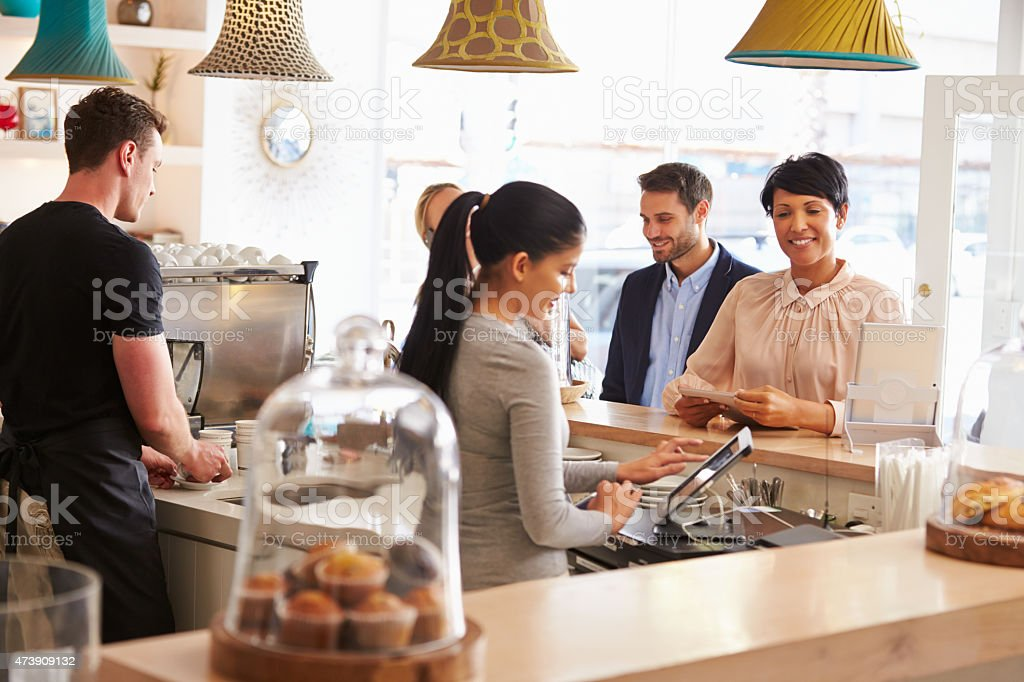 Cashier taking an order in cafe stock photo