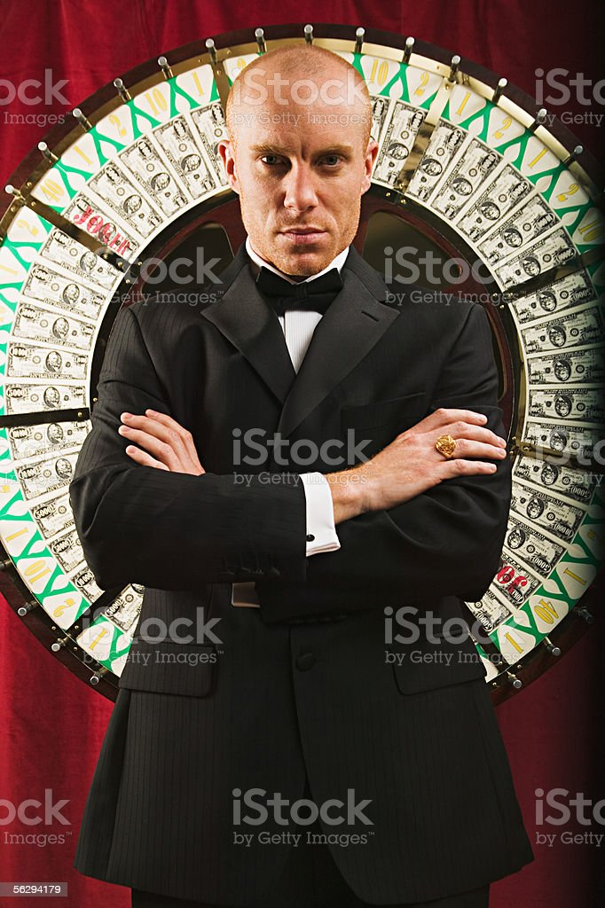 Casino worker in front of the wheel of fortune stock photo