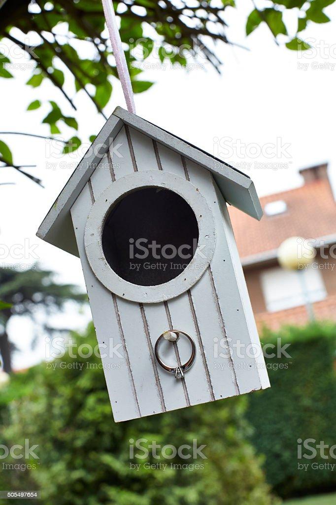 Casita de madera blanca para pájaros con anillo de boda. stock photo