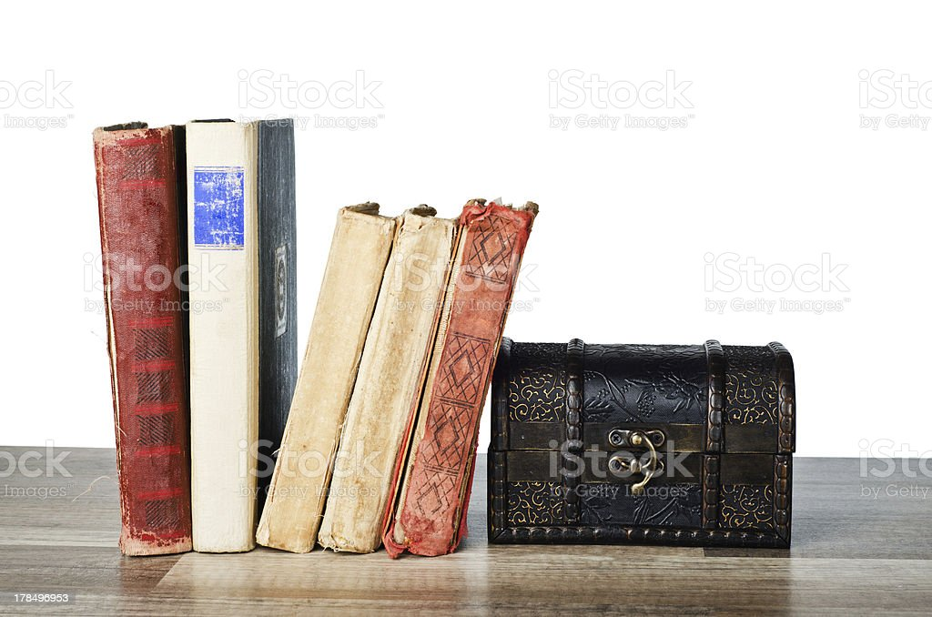 casket and old book on a wooden surface stock photo