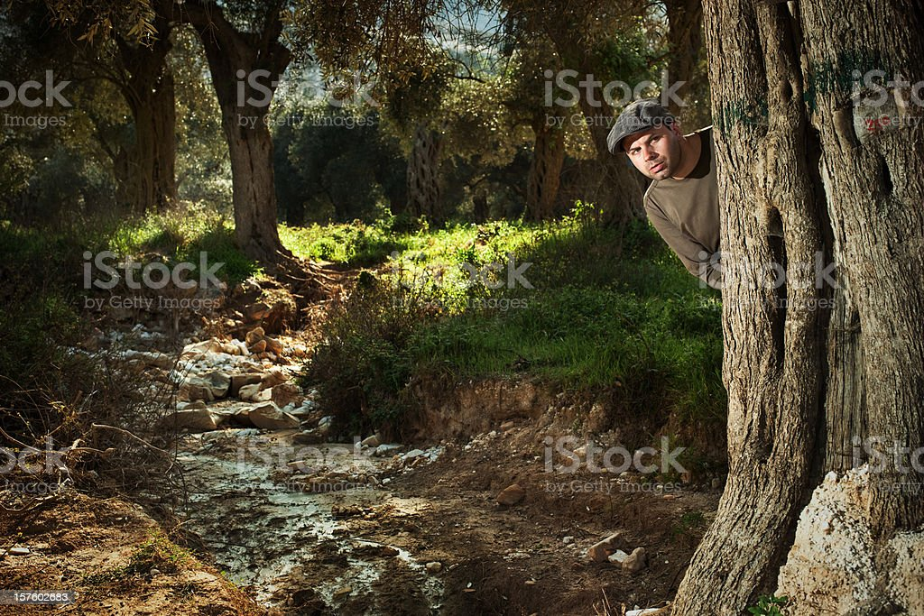 Casquette man is looking suspiciously behind a tree royalty-free stock photo