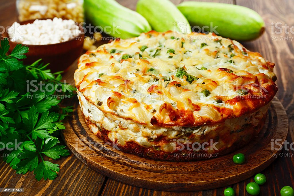 Casserole of pasta with green peas, zucchini and curd stock photo