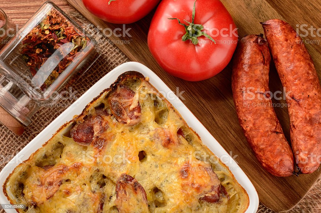 Casserole with potatoes, sausages, tomatoes and cheese. stock photo